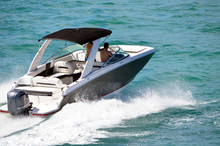 Angled View Of A Motor Boat With Black Canvas Canopy And One Outboard Engine.