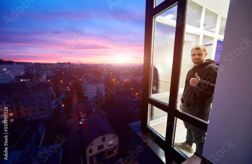 Man is standing on a balcony with panoramic windows and showing a thumb up like sign with a magical sunset outside the window Canvas Print