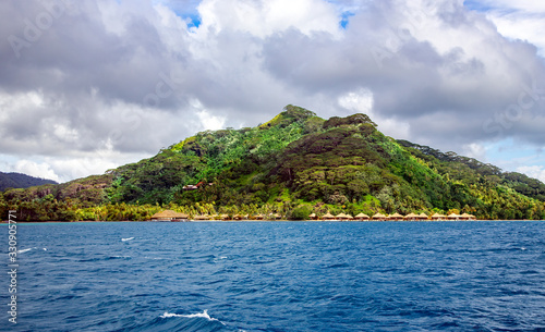 Fotografia Luxury overwater thatched roof bungalow resort on the background of mountains with rain forests on Bora Bora in French Polynesia