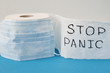 Leinwanddruck Bild - Panic buying Covid-19 Coronavirus outbreak concept. Roll of toilet paper with inscription stop panic and surgical mask on the blue background.