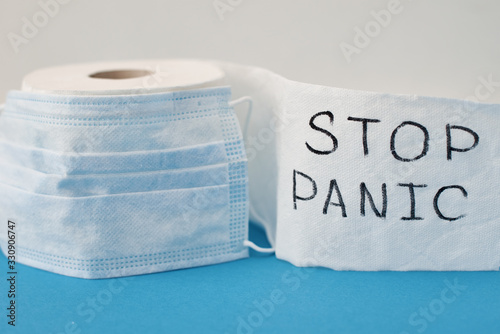Obraz Panic buying Covid-19 Coronavirus outbreak concept. Roll of toilet paper with inscription stop panic and surgical mask on the blue background. - fototapety do salonu