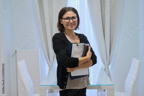 Obraz Mature woman social worker, psychologist near window with business papers - fototapety do salonu
