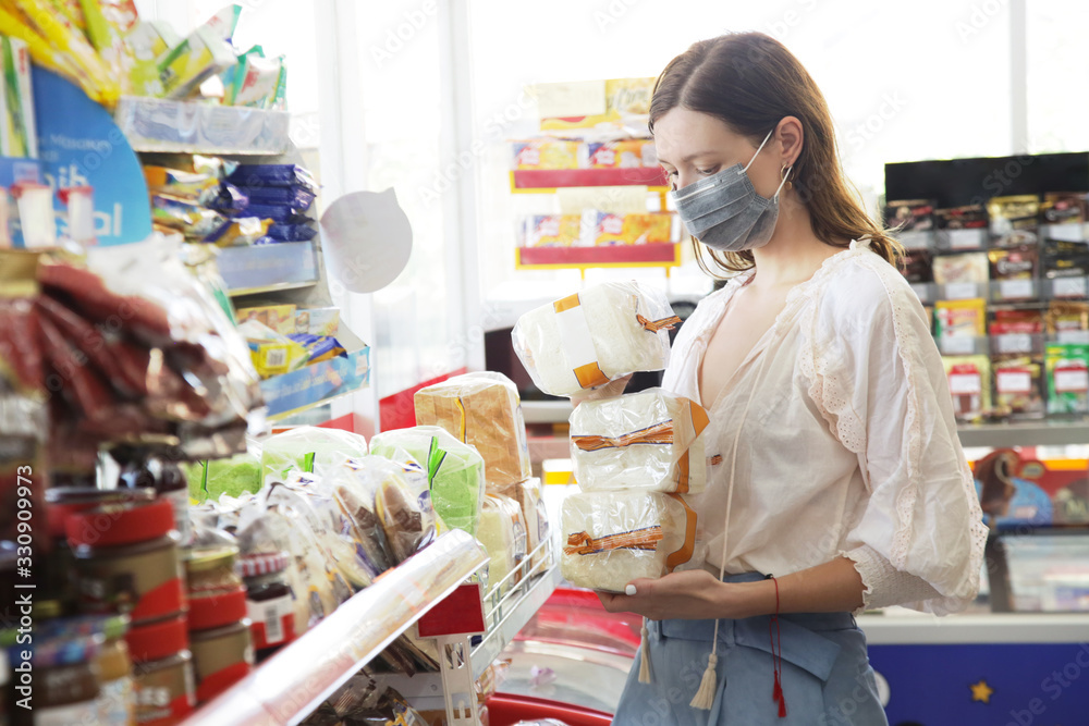 Fototapeta  Woman wearing protective mask while grocery shopping in supermarket, Coronavirus contagion fears concept