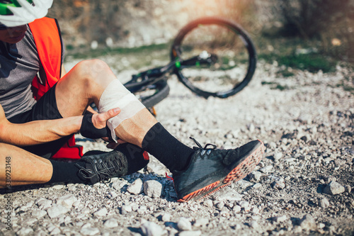 Fototapeta The biker fell from a bike, using a bandage from his first aid kit to help himself. Bicycle accident. obraz