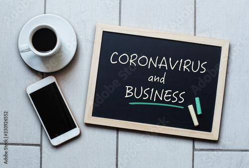 Fototapeta Coronavirus and Business text written on blackboard. obraz