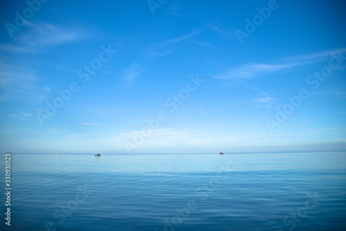 Two boats floating on the sea under the blue sky; beautiful seascape