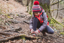 Portrait Of Girl On Hiking Forest Trip Tying Shoe Laces.