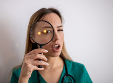 Young Attractive Woman Looking Through Magnifying Glass