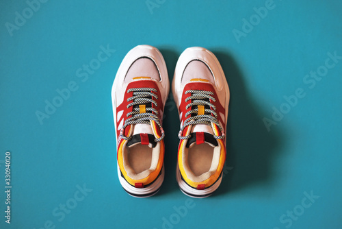 Fotografia Women's multi-colored sneakers on a turquoise background.