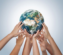 Many Children Hands Holding Planet Earth Isolated On Blue Background With Copy Space