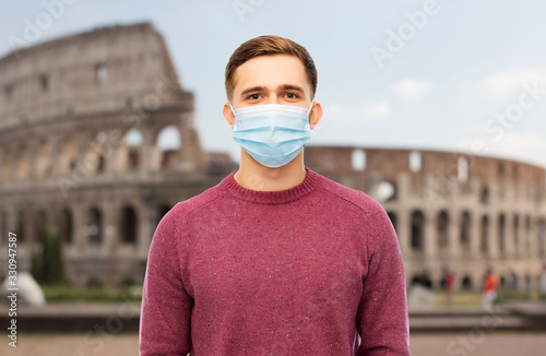health, safety and pandemic concept - man wearing protective medical mask for protection from virus disease over coliseum in rome, italy background