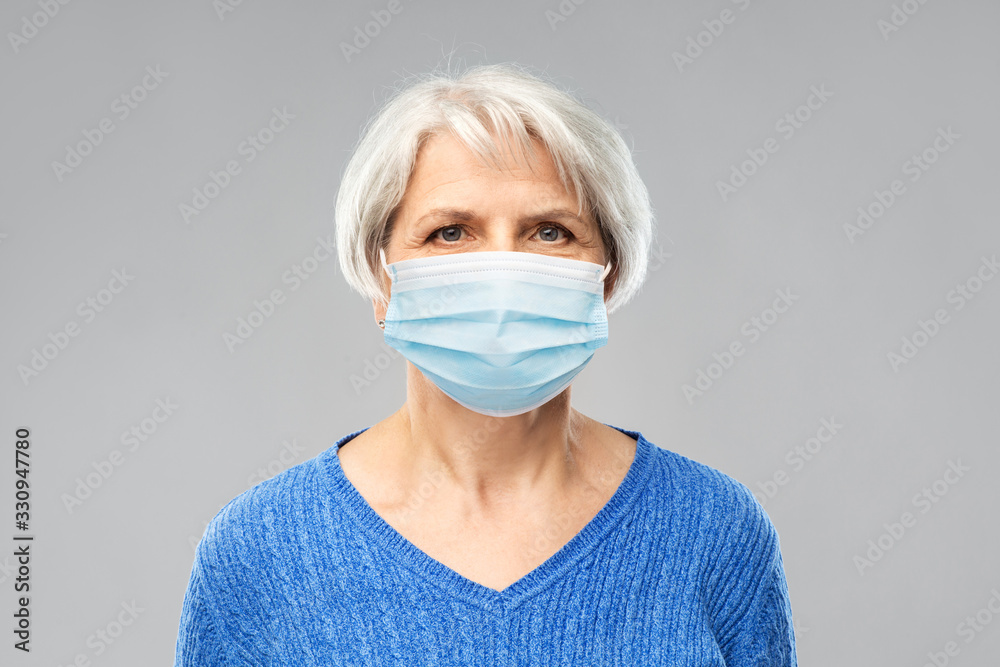 Fototapeta health, safety and pandemic concept - portrait of senior woman wearing protective medical mask for protection from virus over grey background