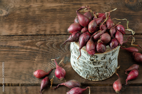 Photo Red seeding onion in birchen pot on wooden background