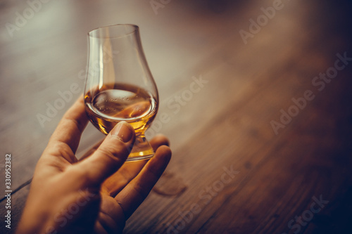 Cuadros en Lienzo Hand holding a Glencairn whisky glass