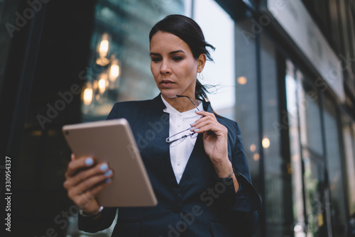 Fotomural Thoughtful businesswoman reading information on tablet in urban street