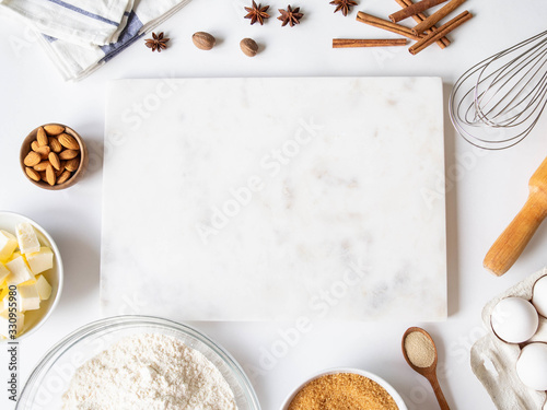 Foto Frame of various baking ingredients - flour, eggs, sugar, butter, dry yeast, nuts and nuts, kitchen utensils and white marble board