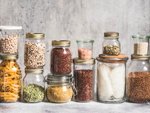 Glass Jars With Various Cereals And Seeds - Peas Split, Sunflower And Pumpkin Seeds, Beans, Rice, Pasta, Oatmeal, Lentils, Bulgur On A Grey Background