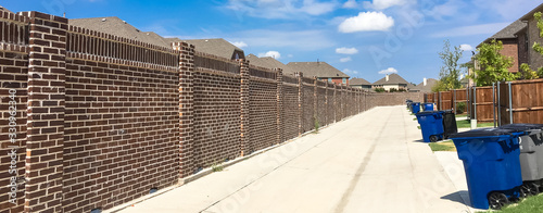 Panoramic concrete back alley with trash containers of new residential housing i Wallpaper Mural