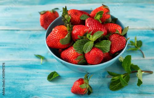 Fototapeta Close up of a fresh strawberry in a blue bowl on light blue background obraz