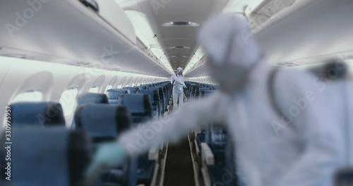 Obraz HazMat team in protective suits decontaminating airplane cabin during virus outbreak - fototapety do salonu