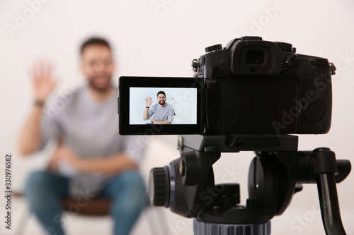 Obraz Young blogger recording video indoors, focus on camera screen - fototapety do salonu