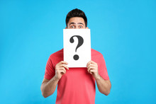 Emotional Young Man With Question Mark Sign On Light Blue Background