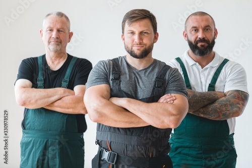 Foto Crew of three professional builder wearing overalls standing in empty interior