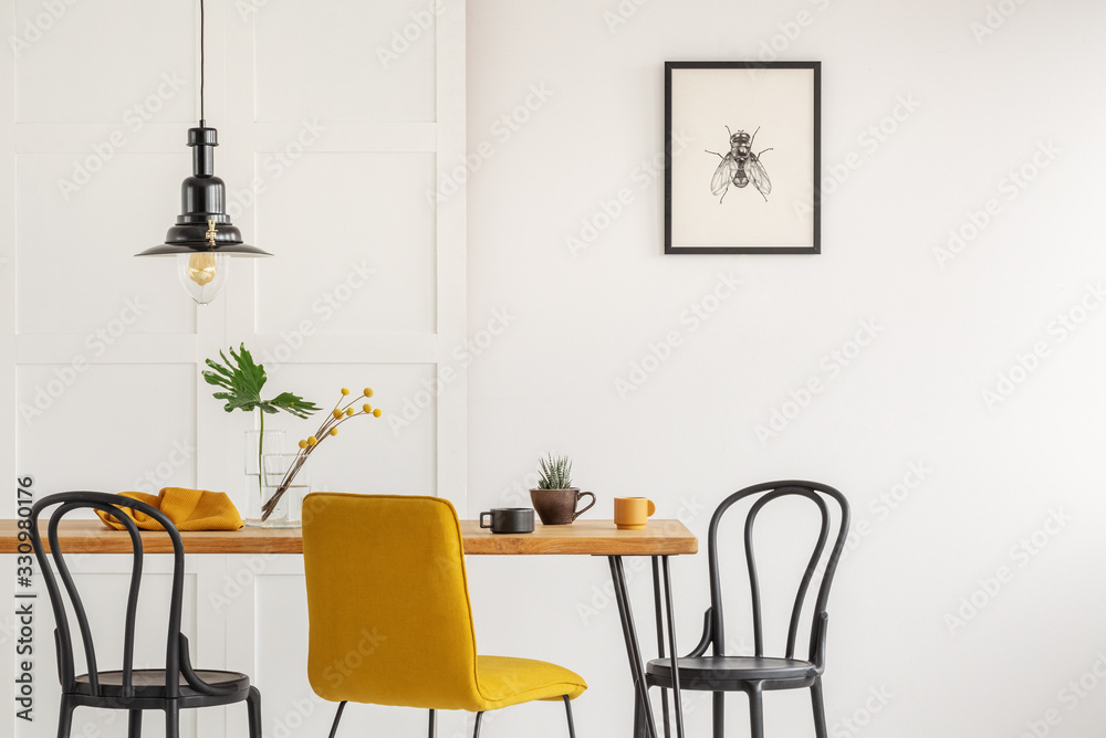 Fototapeta Stylish yellow chair at wooden dining table in trendy interior