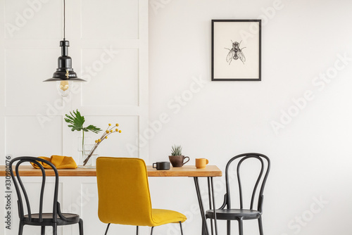 Stylish yellow chair at wooden dining table in trendy interior