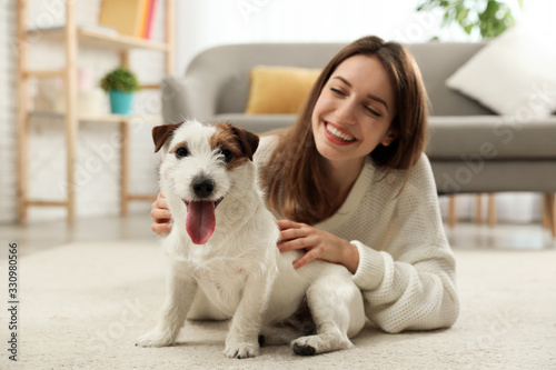 Obraz Young woman with her cute Jack Russell Terrier at home. Lovely pet - fototapety do salonu