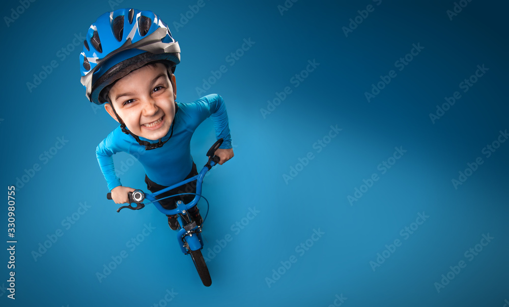 Fototapeta funny little boy with a bicycle in a helmet on a blue background. top view. studio photo
