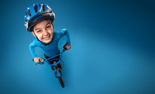 Funny Little Boy With A Bicycle In A Helmet On A Blue Background. Top View. Studio Photo