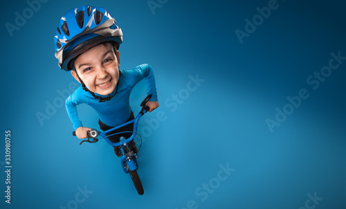Photo funny little boy with a bicycle in a helmet on a blue background