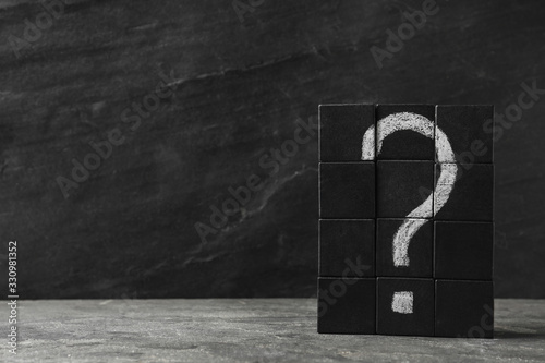 Fototapeta Wooden cubes with question mark on grey stone table