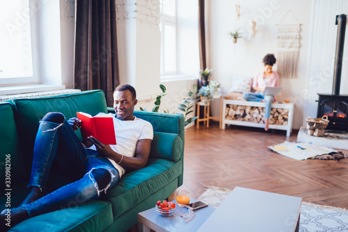Black man reading book on sofa while woman on bench