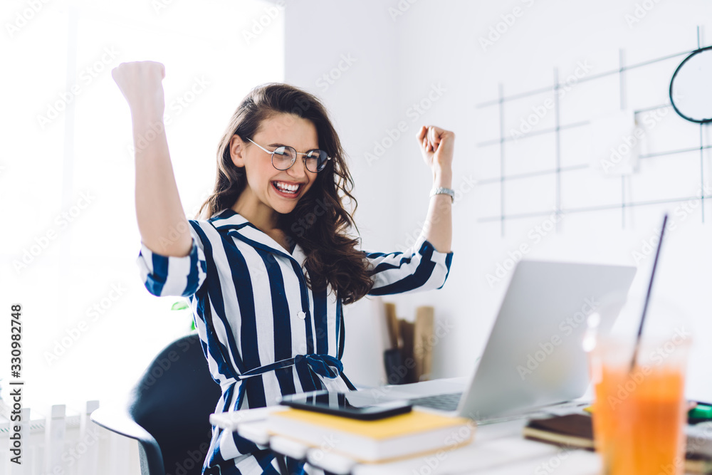 Fototapeta Excited young woman sitting at table with laptop and celebrating success