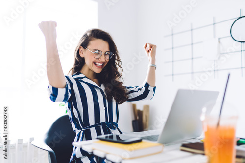 Excited young woman sitting at table with laptop and celebrating success Fotobehang