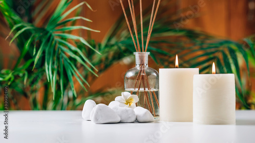 Fototapeta Aromatherapy Concept. Aromatic White Candles and Essential Oil Reed Diffusers obraz
