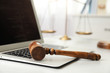 Laptop, wooden gavel and scales on white table, closeup. Cyber crime