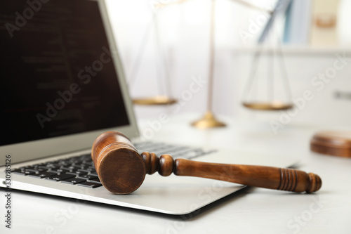 Fotografie, Obraz Laptop, wooden gavel and scales on white table, closeup