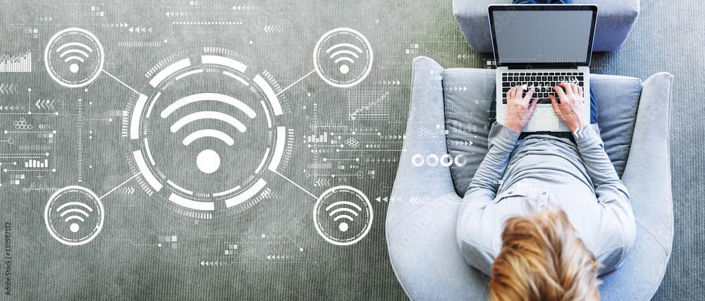 Fototapeta Wifi theme with man using a laptop in a modern gray chair