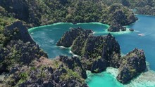 Tropical Twin Lagoon At Coron Island With Turquoise And Blue Water And A Boat Entering The Bay Of Huge Green Rocks Protruding From The Water