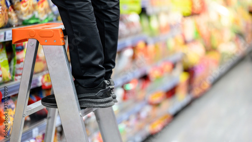 Fotografía Male storekeeper legs standing on aluminum stair putting products on shelves in grocery store or supermarket