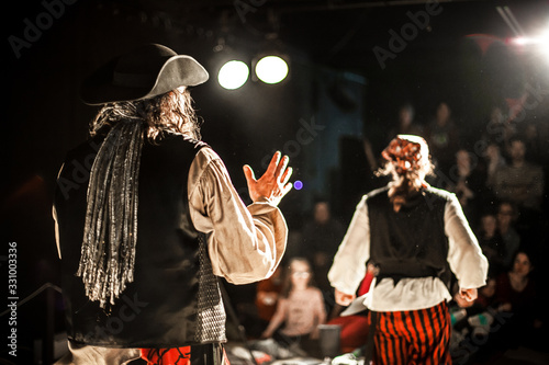 Photo A creative shot with shallow depth of field from behind two performing arts entertainers dressed as pirates on a theater stage during comedy act