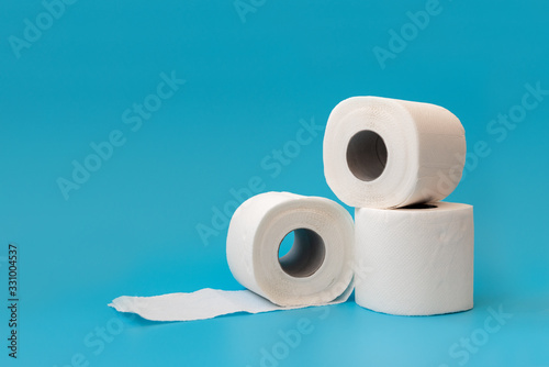 Several rolls of toilet paper lying on blue background Canvas Print