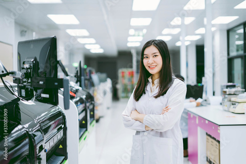 young smiling scientist in white lab coat standing with automation blood analyze Wallpaper Mural