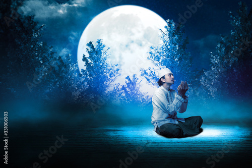 Photo Young man Asian moslem pray on the night with mosque and moon background