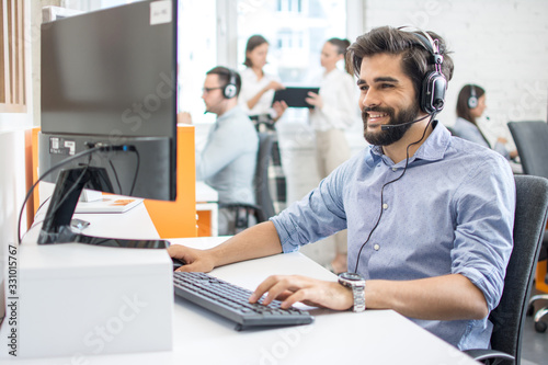 Fotografia Smiling friendly helpline technical support agent with hands-free headset at call centre