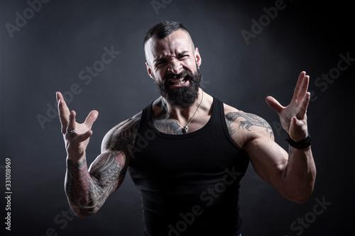 Photo Uomo con barba compeltamente tatuato in canottiera guarda molto irritato con , l