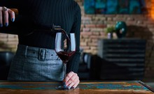Woman Pouring Red Wine Into Wi...